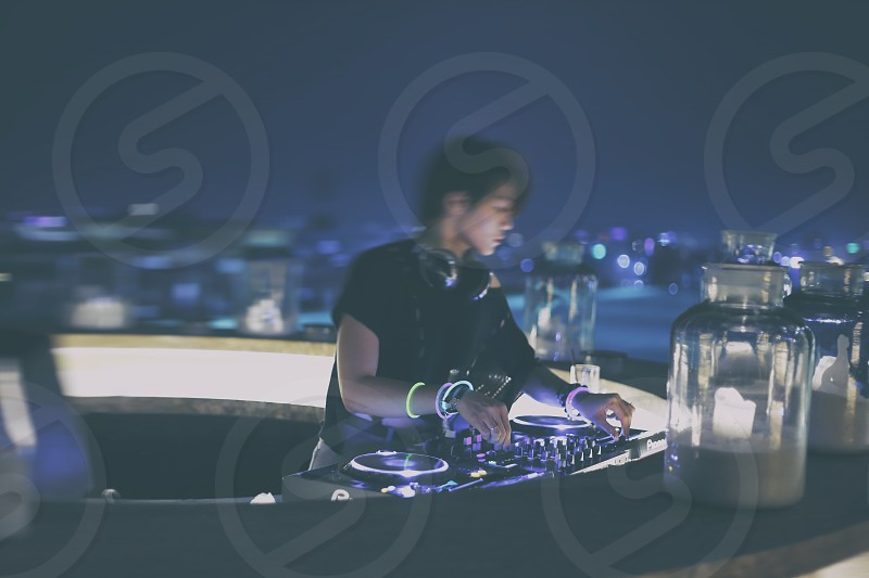 live performance of DJ on a roof top bar at night photo