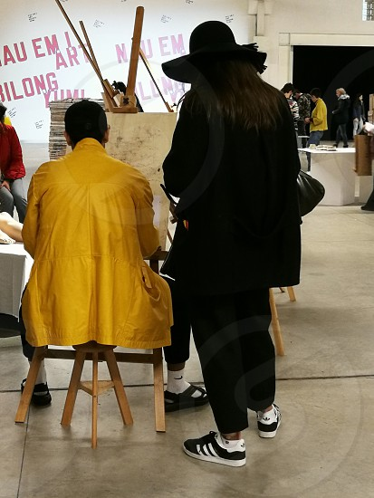 woman wearing black sunhat and black coat standing while facing on man wearing yellow jacket facing on sketch pad in easel photo