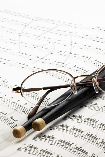 music charts with drums stick and glasses on top photo