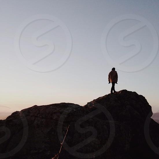 man standing in rocky mountain dusk photo