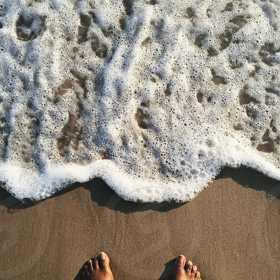 barefooted person on beach with white sea foam photo