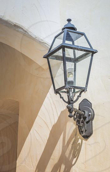 old vintage metal light with a modern led light inside against a white stone wall in sardinie photo