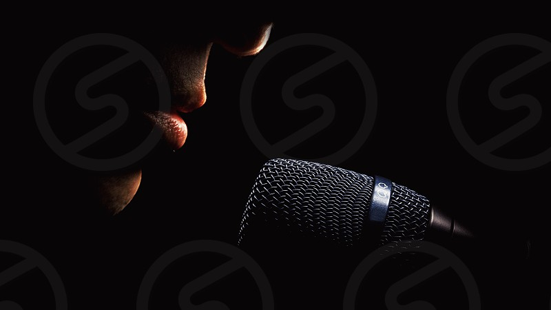 Part of a singer face details of mouth and modern black microphone on black background.  photo