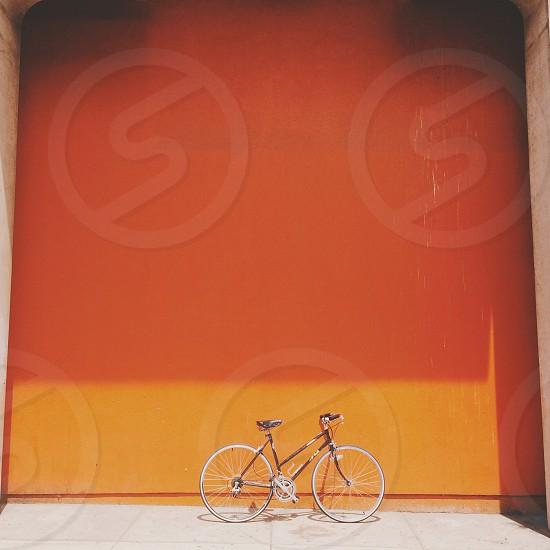 white and black bicycle near orange wall photo