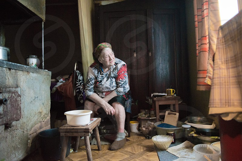 Old woman sitting at home   photo