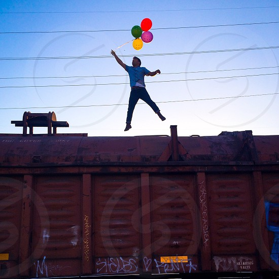 man in blue button down shirt jumping up holding balloons on red train photo