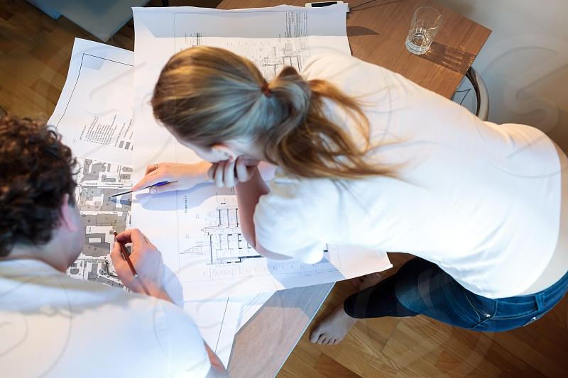 High angle shot of male and female architects at work. Woman pointing on the place on the map photo
