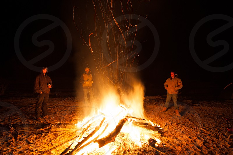 photo of 3 people standing near campfire during night time photo