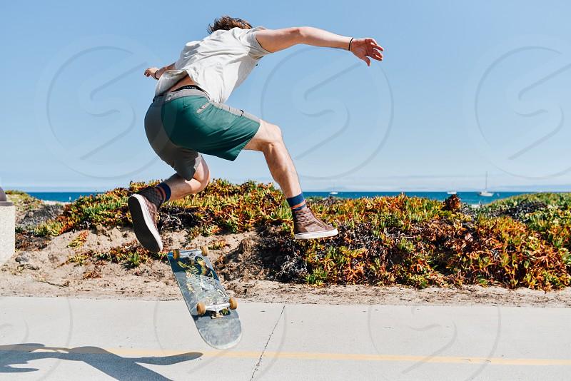 skateboard skater feet shoes man socks shorts beach ocean california photo