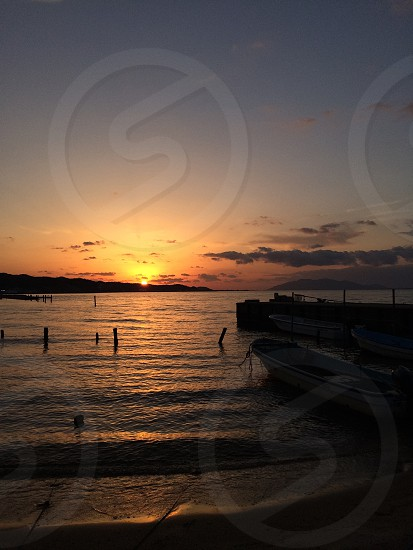 sunset over beach and people swimming photo