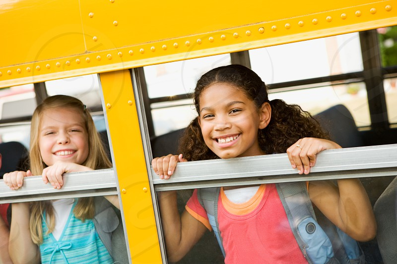 Young girls on school bus.  school bus student school education bus smiling happy back to school photo