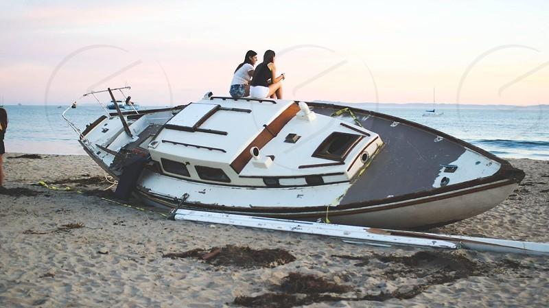 two women sitting on yacht on seashore photo
