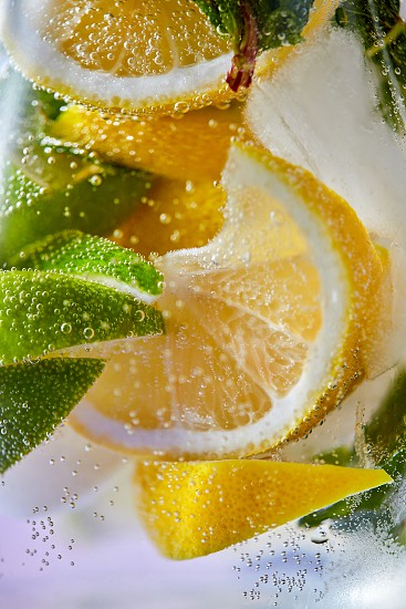 Macro photo of fresh lime and lemon slices with bubbles in the glass. Summer cold drink photo