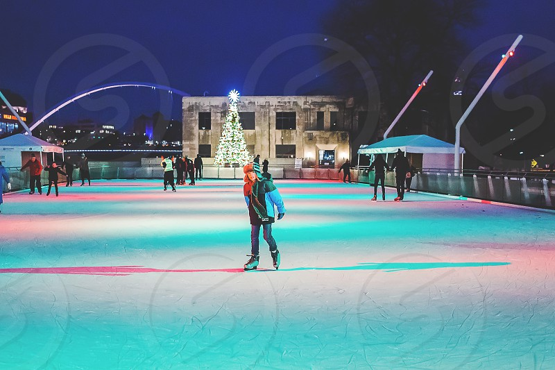 family having fun in the winter while ice skating photo