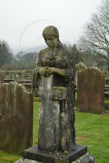 Moss covered tombstone of a lady leaning on a cross and looking solemnly over a grave at Sweetheart Abby in Dumfries Scotland. photo