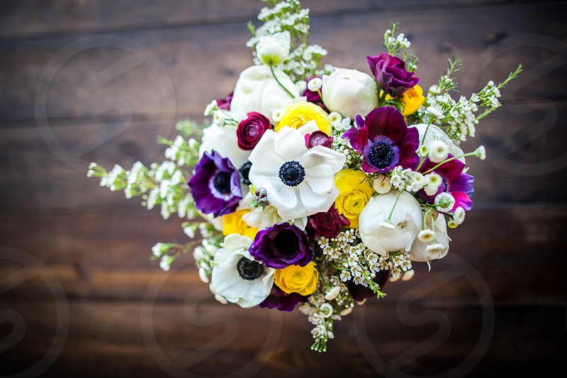 A colorful bridal bouquet resting on a wooden table. photo