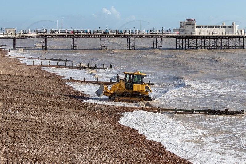WORTHING WEST SUSSEX/UK - NOVEMBER 13 : Bulldozer repairing sea defences in Worthing West Sussex on November 13 2018. Unidentified people. photo
