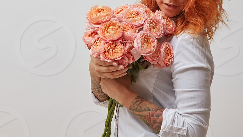 red-haired girl with a tattoo on her arm holding a bouquet of pink roses valentine's day mother's day photo