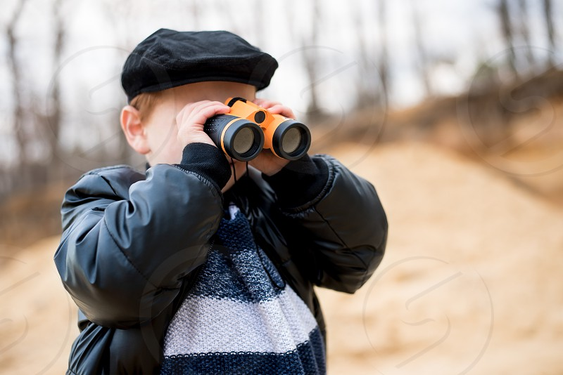 Boy wearing hat looking through binoculars and playing with explorer set on a cold and sunny winter day. photo