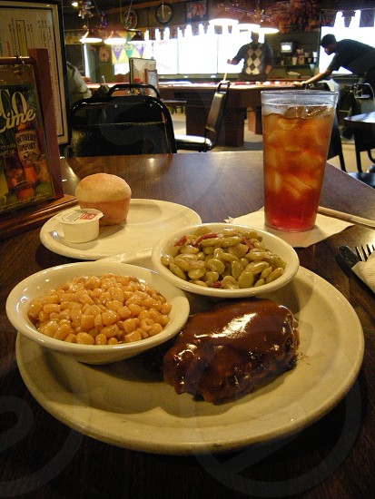Lunch plate Salisbury steak with corn butter beans and roll with iced tea photo