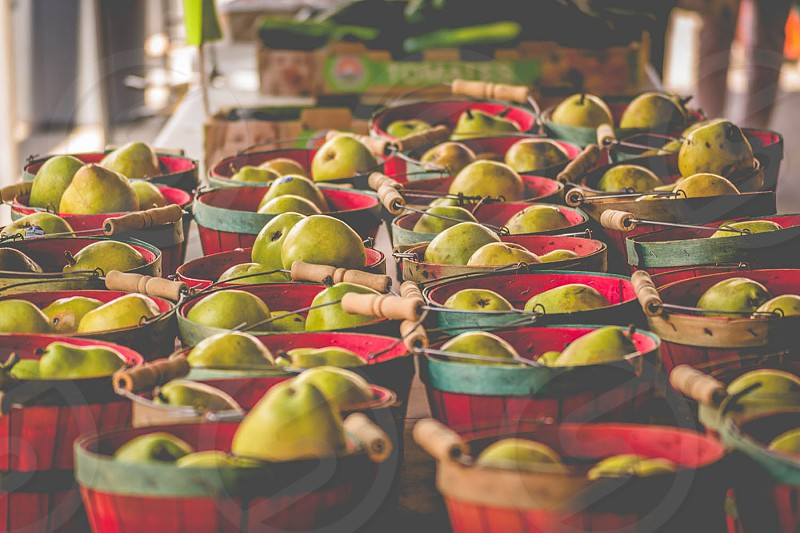 green fruits on red wooden pails photo