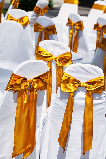 Back side of a group of white chairs with shiny gold sash organza decoration for beach wedding venue preparation photo
