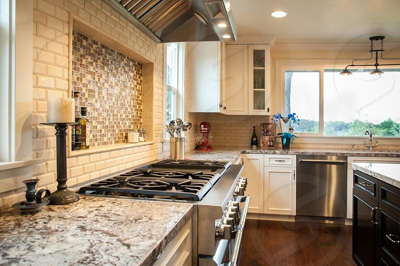 Beautiful contemporary kitchen. Custom backsplash. Stainless steel. Granite. Range. photo