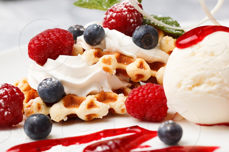Crisp golden waffle served with whipped cream vanilla ice cream and fresh blueberries and raspberries photo