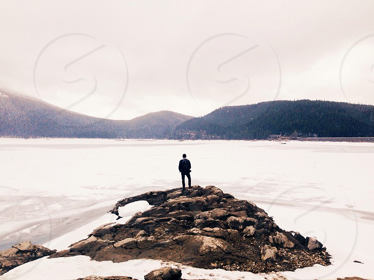 person in black jacket carrying black backpack standing on brown rocks overlooking the snow covered sea photo