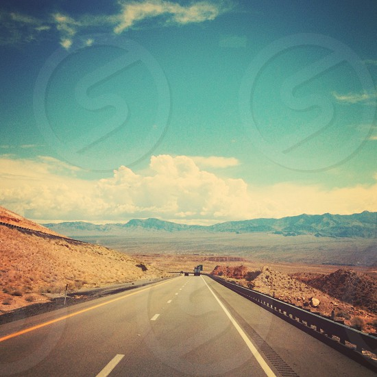 Gray concrete road and view of mountain ranges photo
