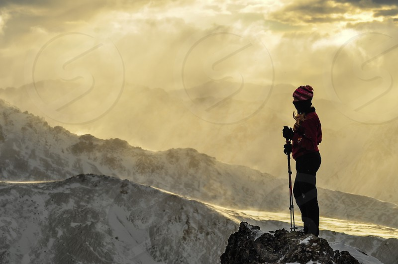 a hiker stands atop wolveriene peak in the frontrange of Chugach State Park Alaska. Clouds and the short winter day created a colorful ambiance photo
