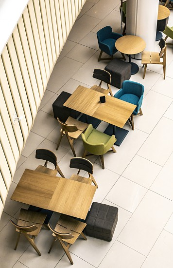 Tables and chairs in cafe. High point of view. No people. Contemporary design of bar furnishings. Coffee shop in a shopping center. photo