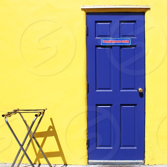 At a theme park a sign on bright blue door on a yellow building reads 'Employees Only. photo