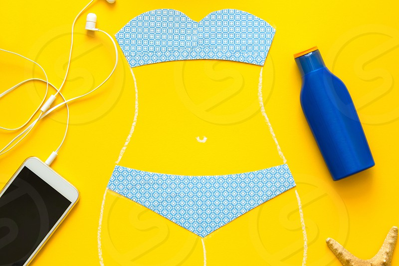 Outlines of girl in paper swimsuit drowing by chalk. Beach accessories. Top view. Flat lay. Summer travel and sun protection concept. Origami. Mock-up photo