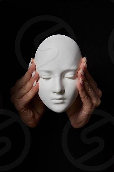 Woman fingers close ears of gypsum mask face on a black background. Hear no evil. Concept three wise monkeys. Place for text. photo