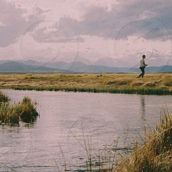 person running along grassy river bank photo