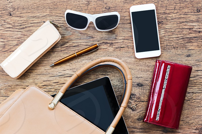 Smartphone sunglasses wallet and other things pulled out of handbag put on a wooden table. Female stuff. Shot from above photo