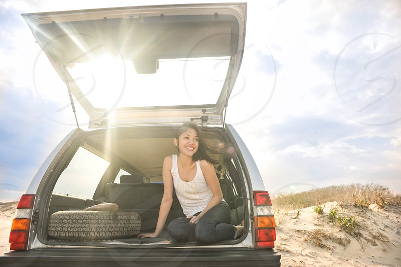 woman with black long hair in white tank top sitting on back of vehicle during daytime photo