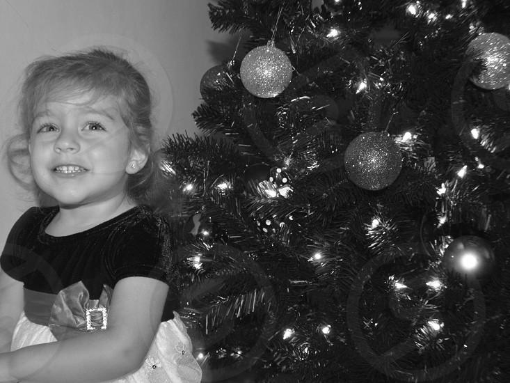 grayscale photo of girl standing beside Christmas tree photo