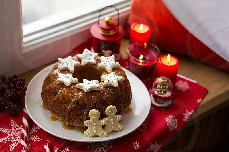 Christmas decoration: cake gingerbread-men and burning red candles on windowsill photo