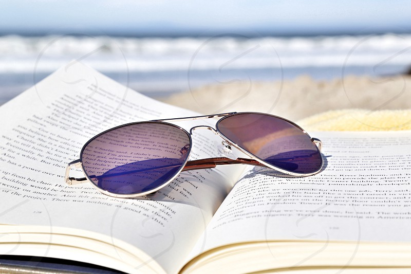 Sunglasses on a Open Book at the Beach photo