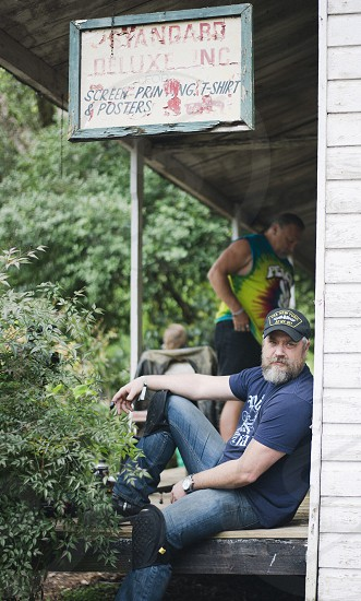 man in jeans and blue t shirt with black knee pads and grey beard sitting on wooden porch photo