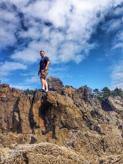 man in blue crewneck t-shirt standing on brown rock photo