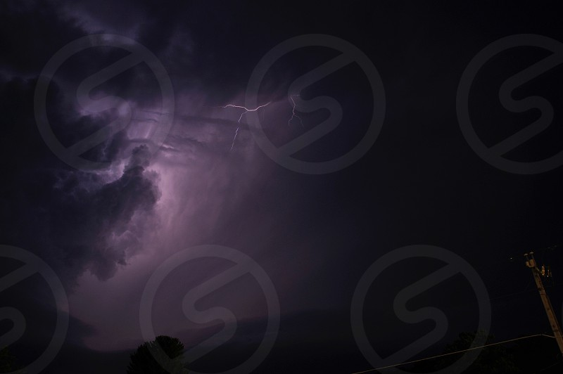 lightning shooting across a dark sky with clouds photo