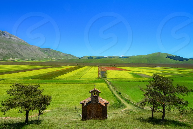 Nature landscape mountain spring flowers green building chapel trees Italy Umbria Norcia scenic viewpoint view travel destination beautiful colorful photo