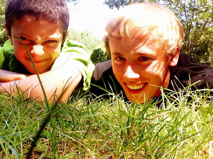 2 man lying in the green grass photo