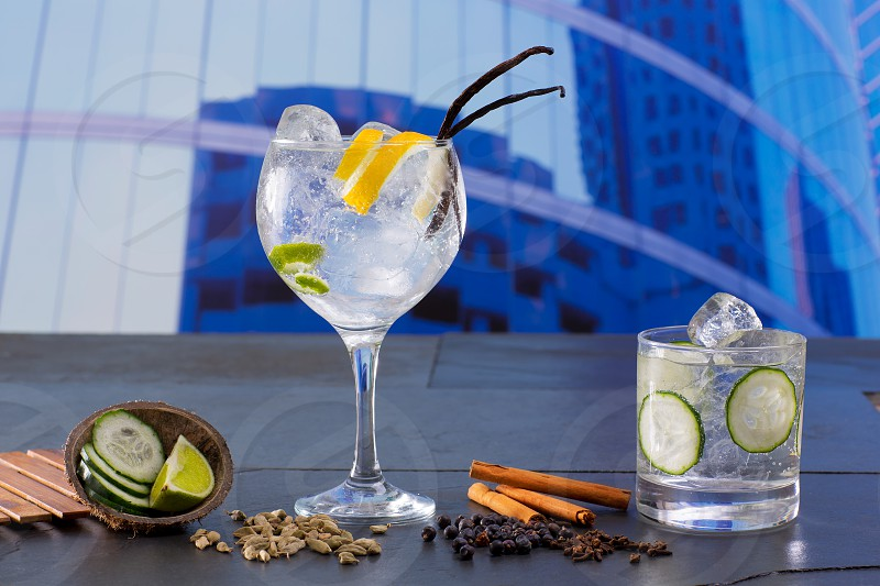 Gin tonic cocktail with spices in urban city buildings background photo