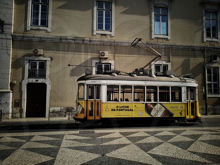 yellow and white tram behind beige wall painted building photo