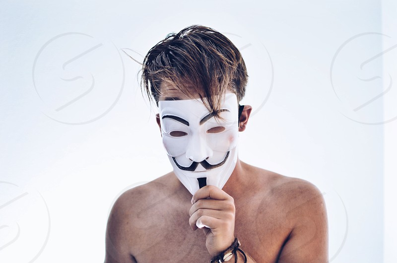 photo of man without tops holding guy fawkes mask in front of his face with black bracelet photo