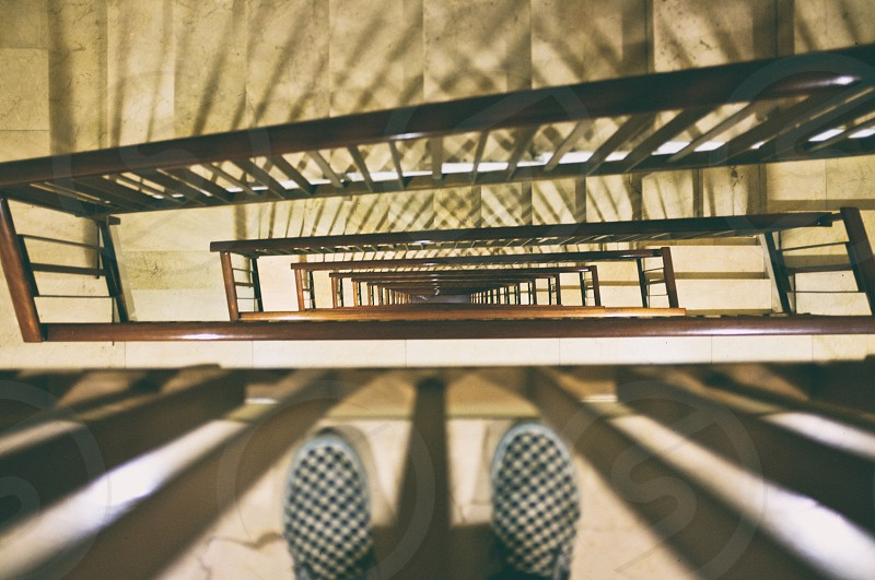 person wearing white and black shoes beside stairs photo
